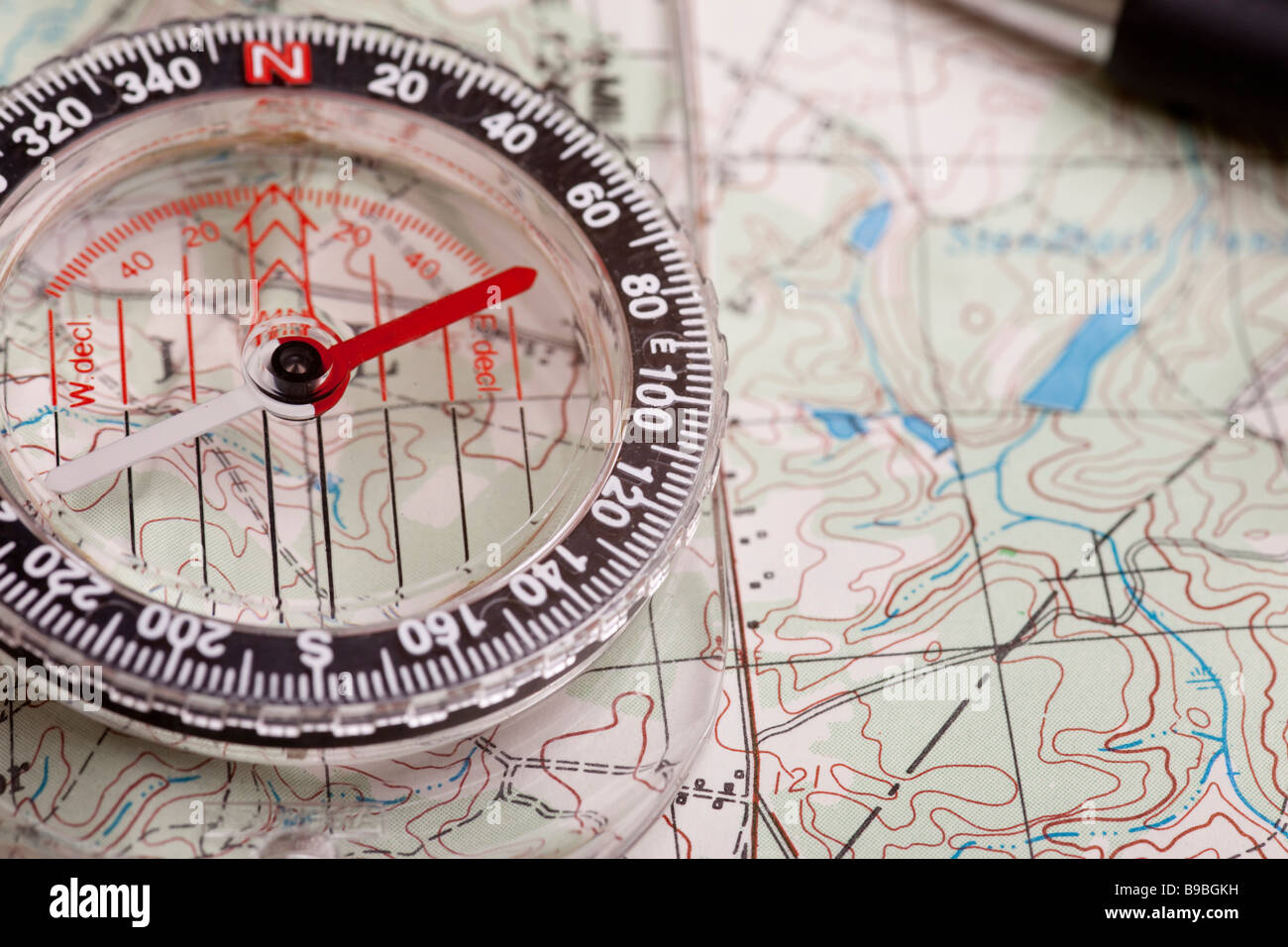 A compass on a topographical map showing terrain features - Stock Image