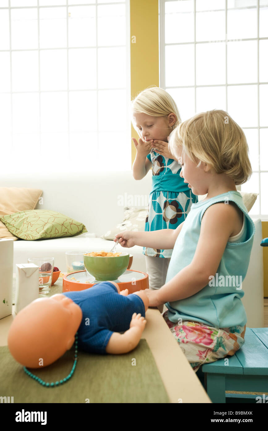 Little girls eating breakfast at messy table - Stock Image