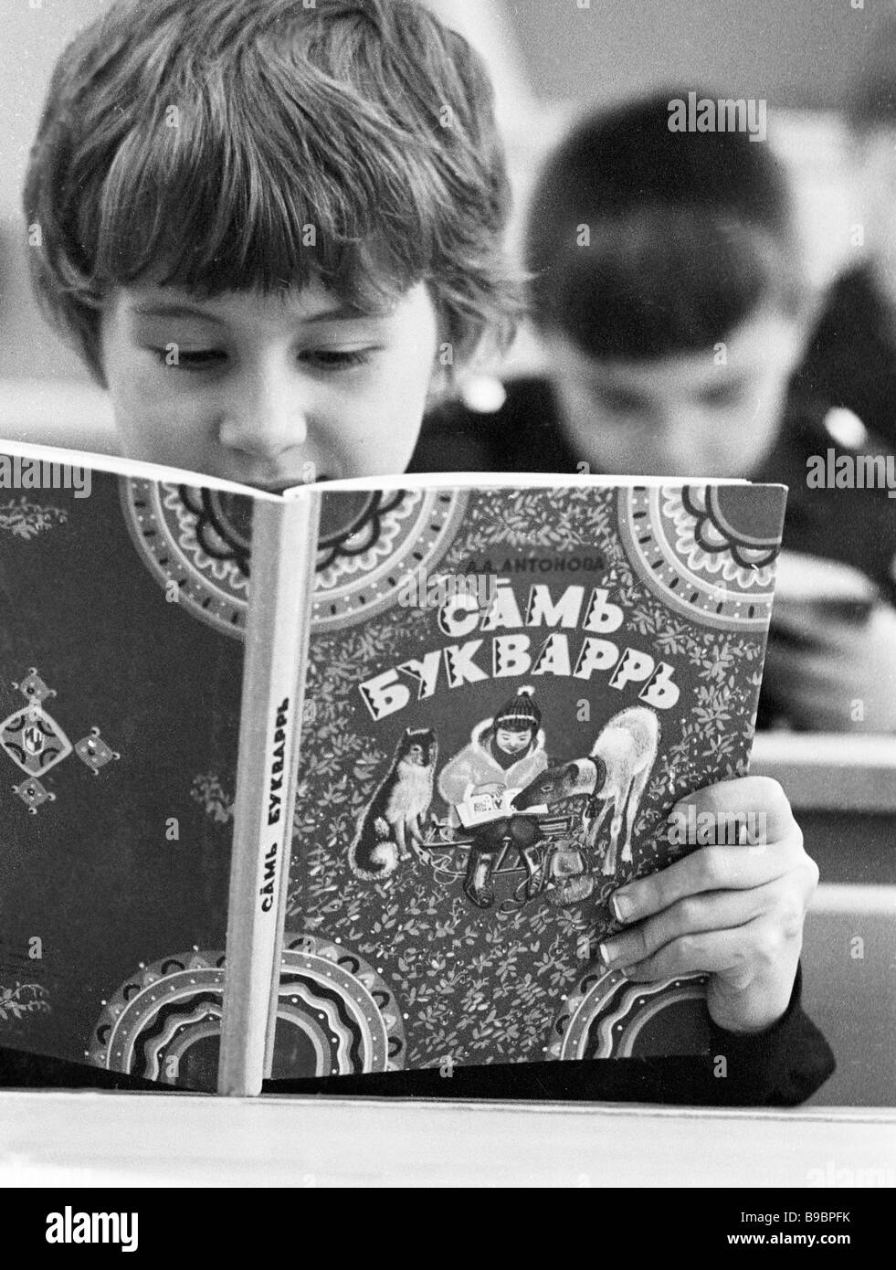 Reindeer breeder s daughter Ira Alexandrova looks at ABC book during reading lesson at Lovozero town s boarding - Stock Image
