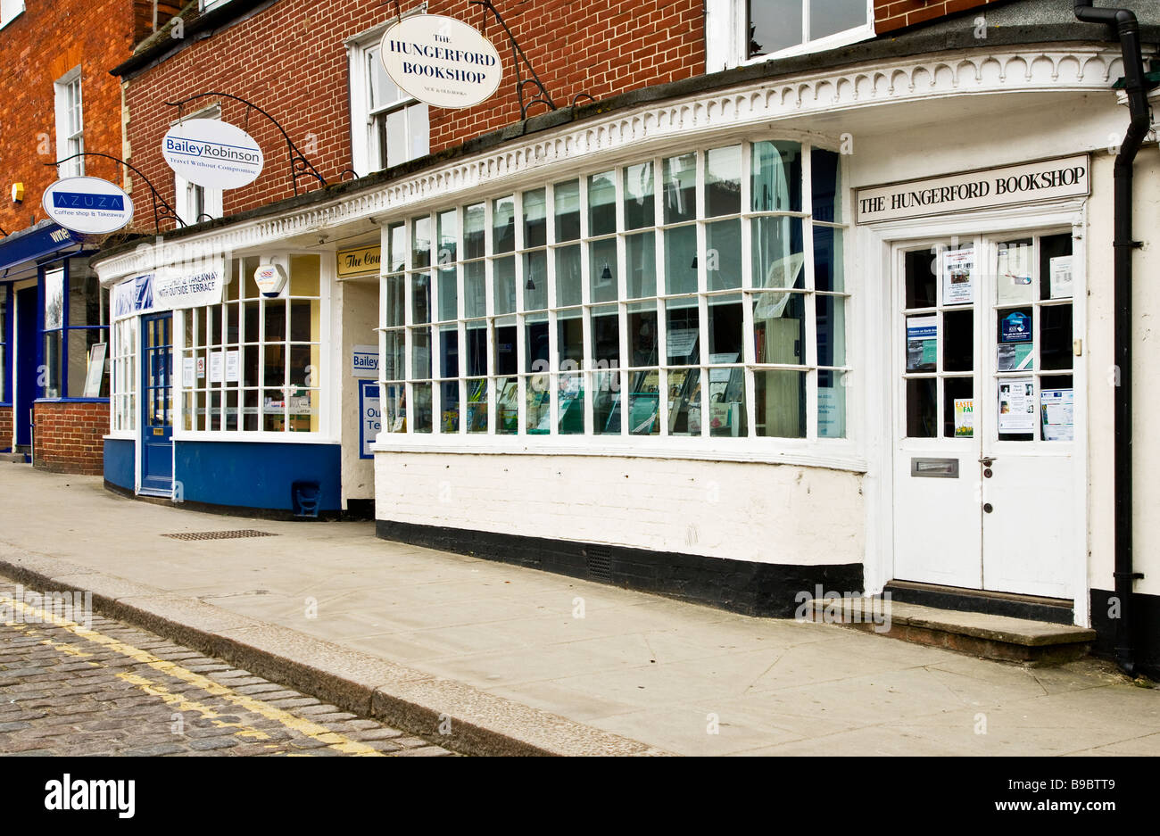 An independent bookshop and others along the High Street in Hungerford Berkshire England UK - Stock Image