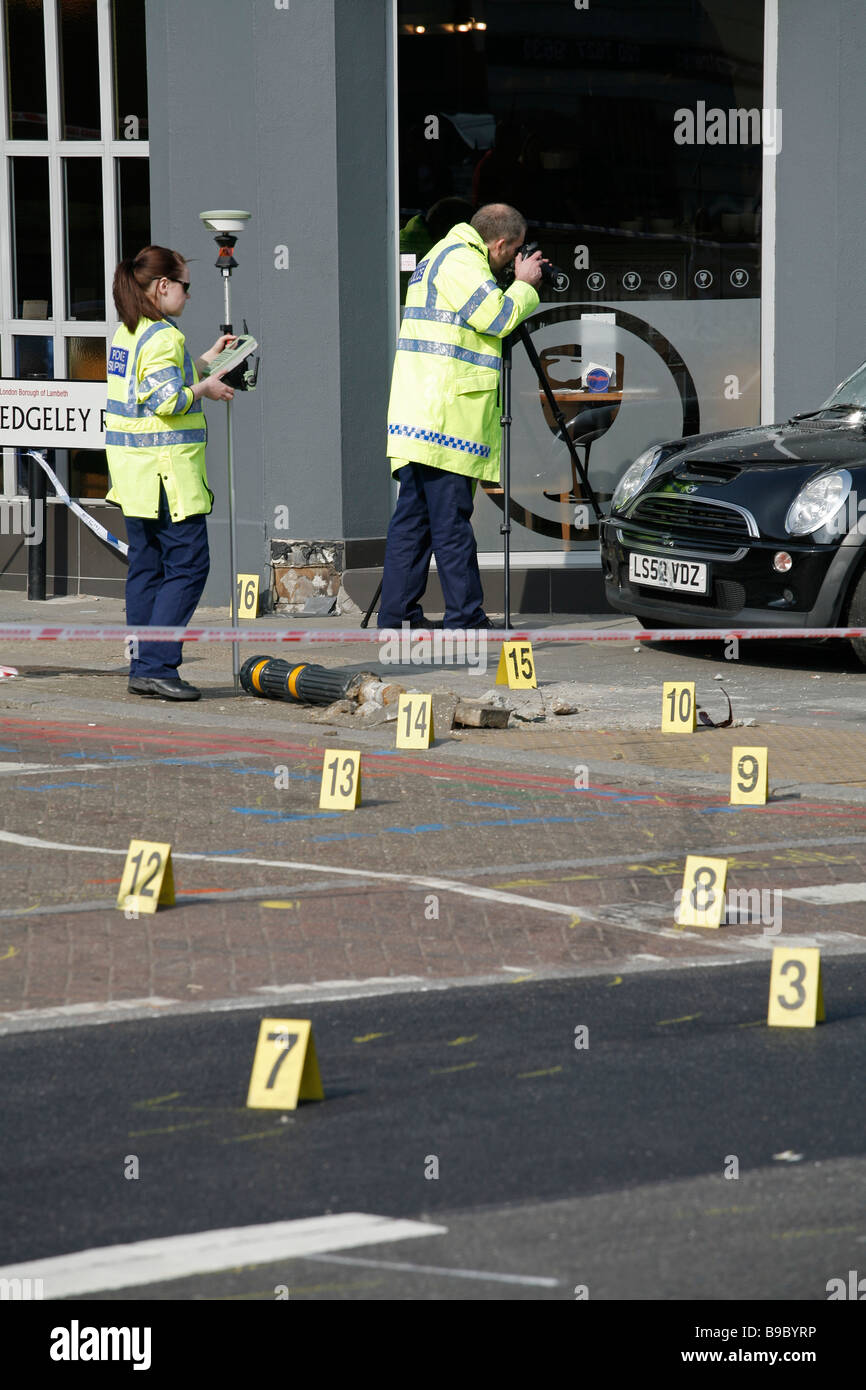 Forensic police take evidence after a road traffic accident leaves a car on the pavement, on Clapham High Street, - Stock Image