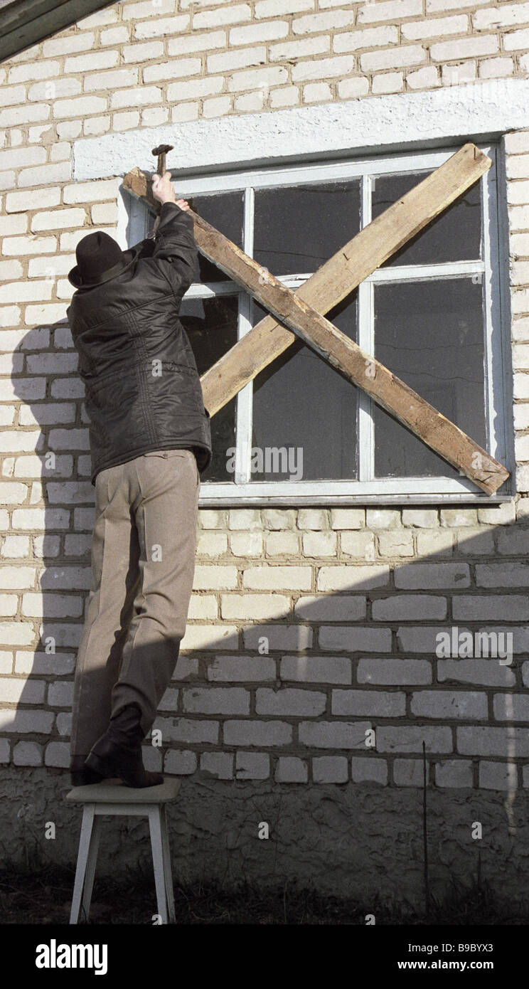 A villager boards up the window of the abandoned house After Chernobyl disaster the radiation in the area exceeds - Stock Image