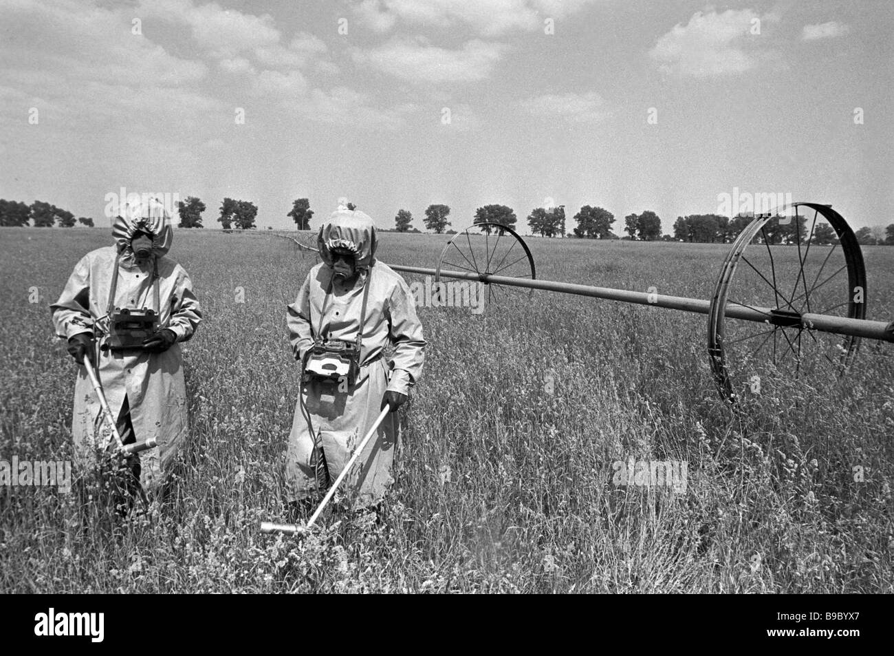 Health physicists in special suits controlling radiation in the fields of the Chernobyl disaster area - Stock Image
