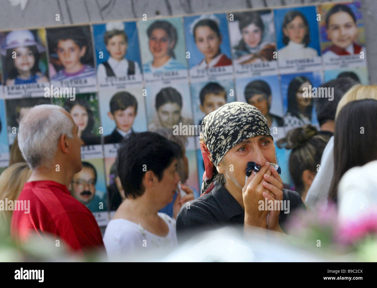 Relatives of the Beslan 2004 school tragedy victims at the wall with photographs - Stock Image
