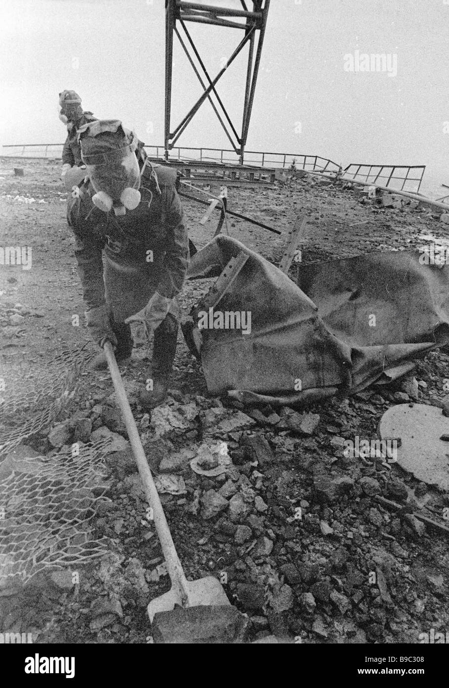 People clean the roof of the damaged reactor after the Chernobyl NPP disaster - Stock Image