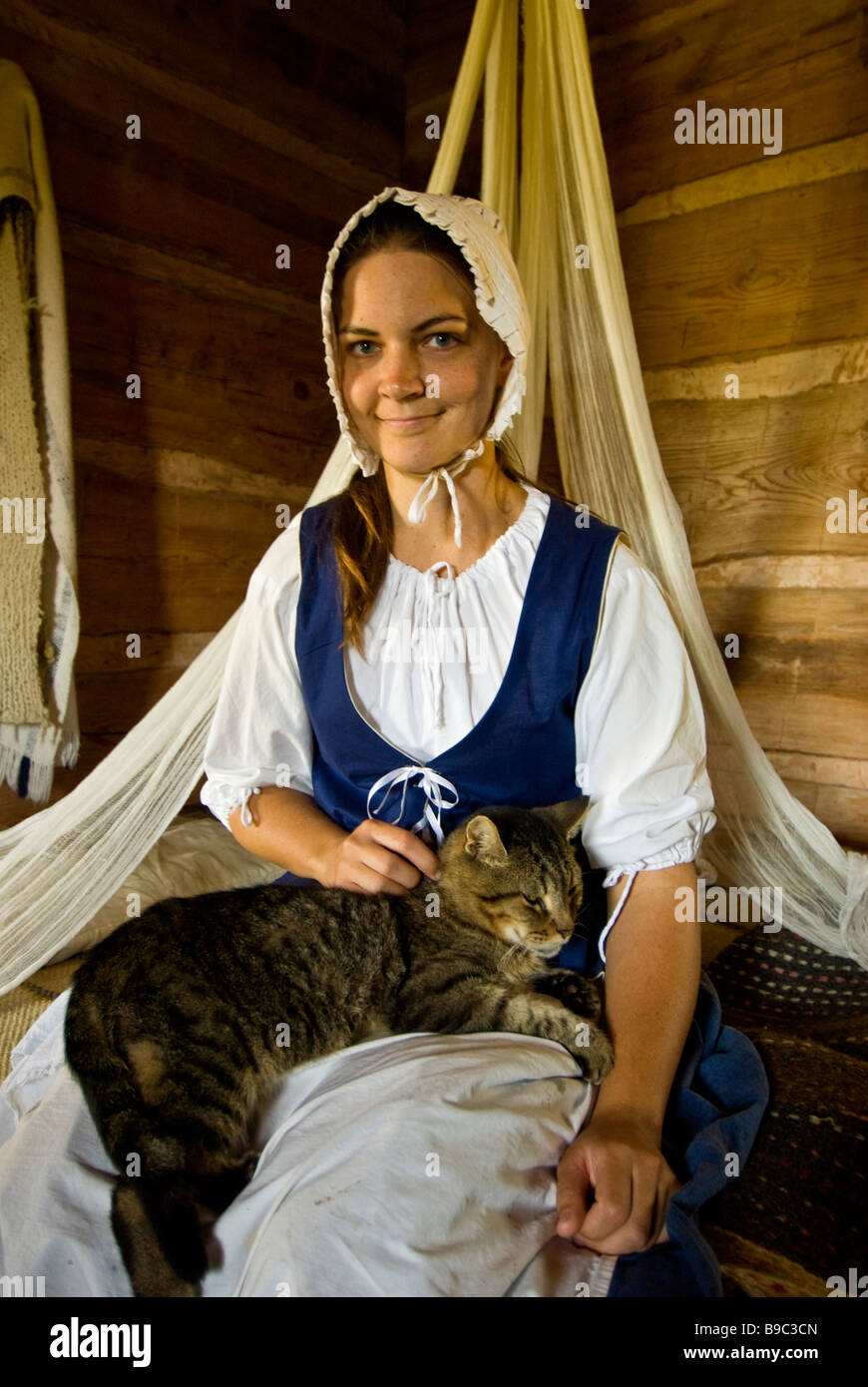 American frontier woman settler in bedroom with cat 1830s Jones Stock Farm George Ranch Historical Park Houston - Stock Image