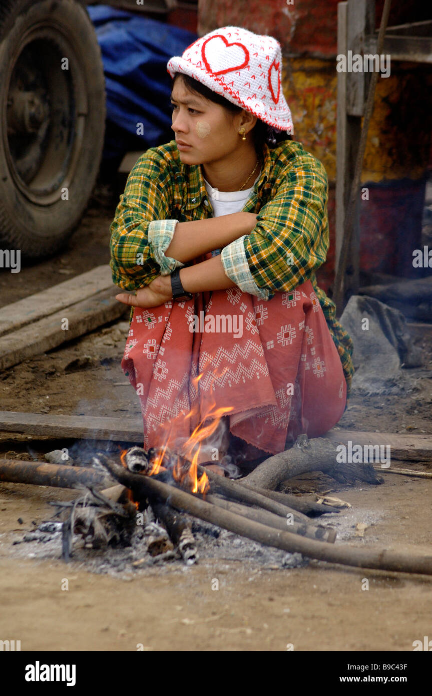 Birmese woman sitting on a small fire on a cold morning at the ferry harbour of Mandalay Myanmar - Stock Image