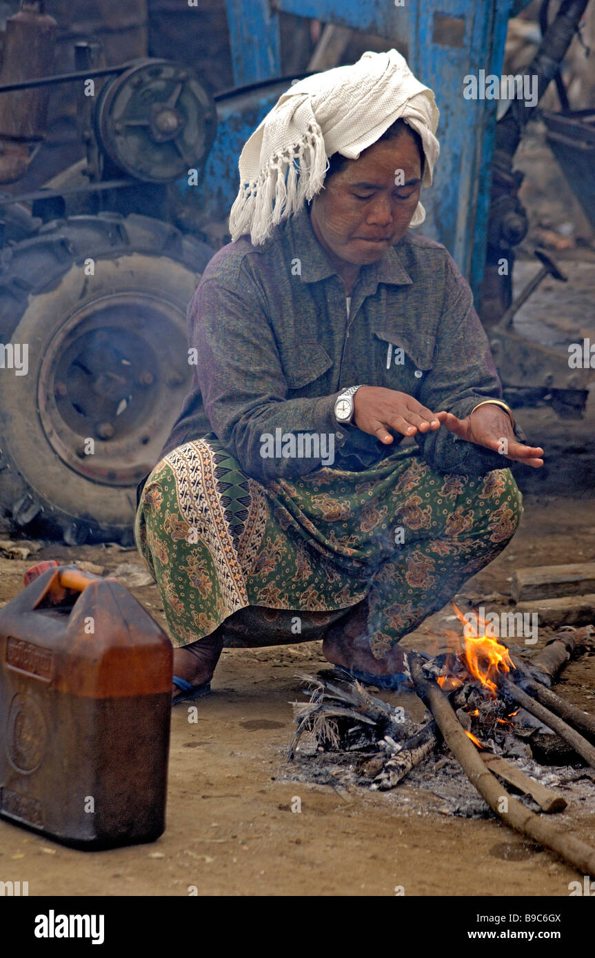 Burmese day labourer sitting on small fire at the ferry station of Mandalay Myanmar Stock Photo