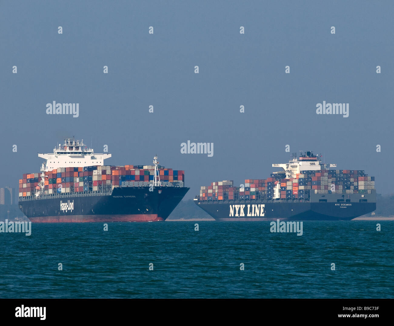 Container ships Houston Express (left) and NYK Oceanus passing each other in Southampton Water UK - Stock Image