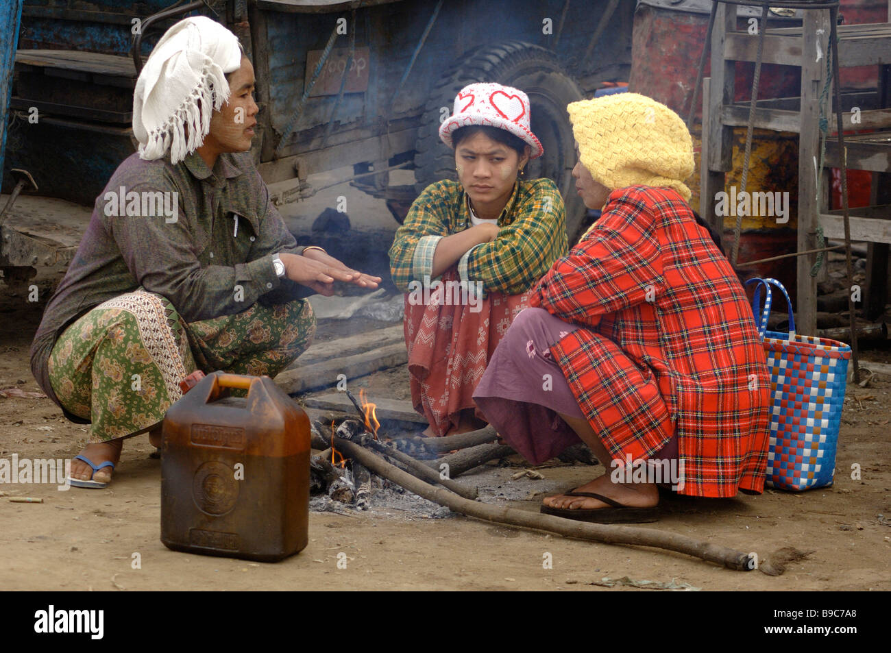 Burmese day labourer sitting on small fire at the ferry station of Mandalay Myanmar - Stock Image