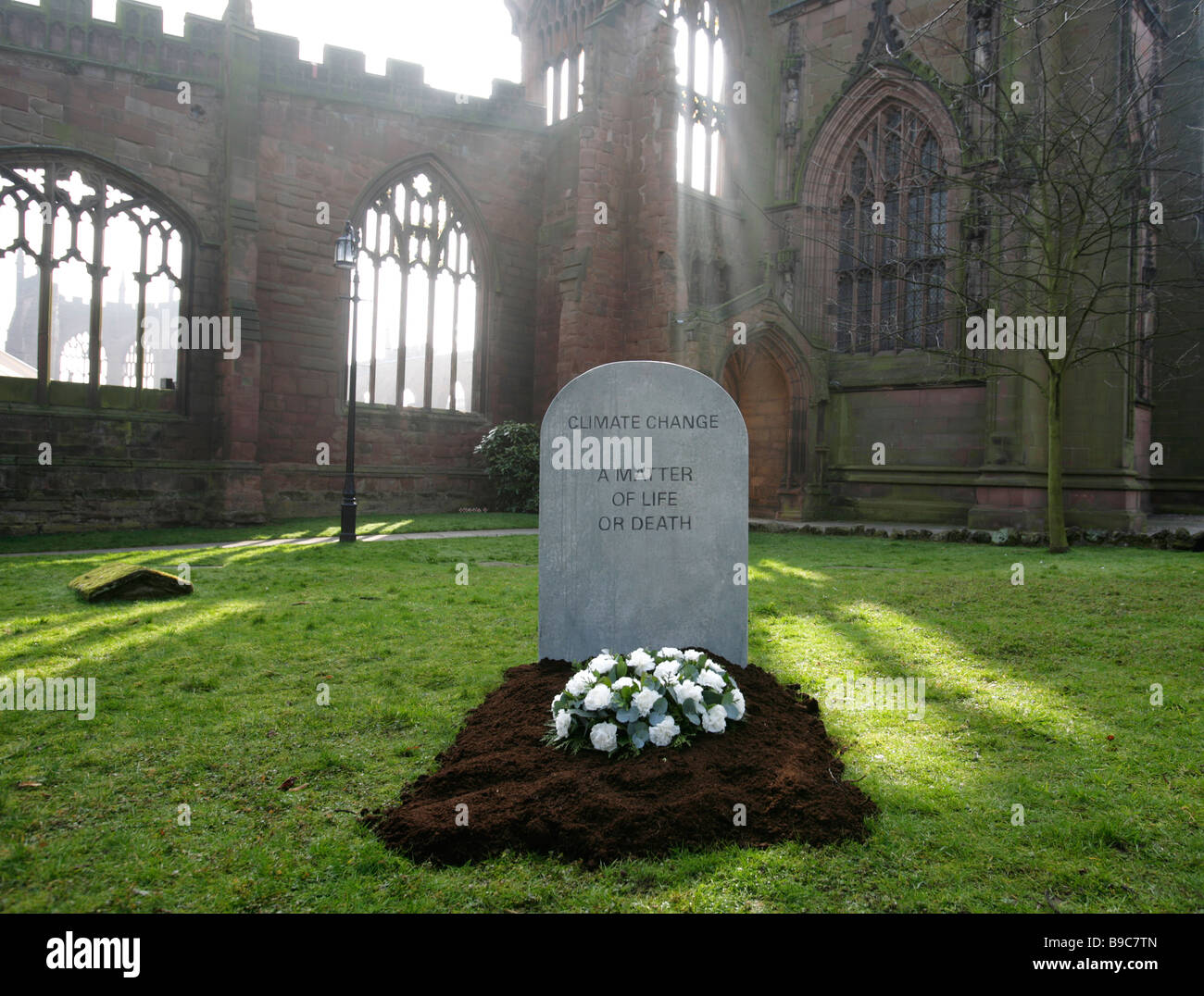 A mock gravestone erected by the Christian Aid charity to represent the people killed by the effects of climate - Stock Image