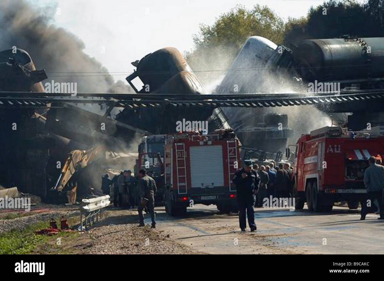 The fire service officers putting out fire in tank cars after the accident when a freight train carrying diesel - Stock Image