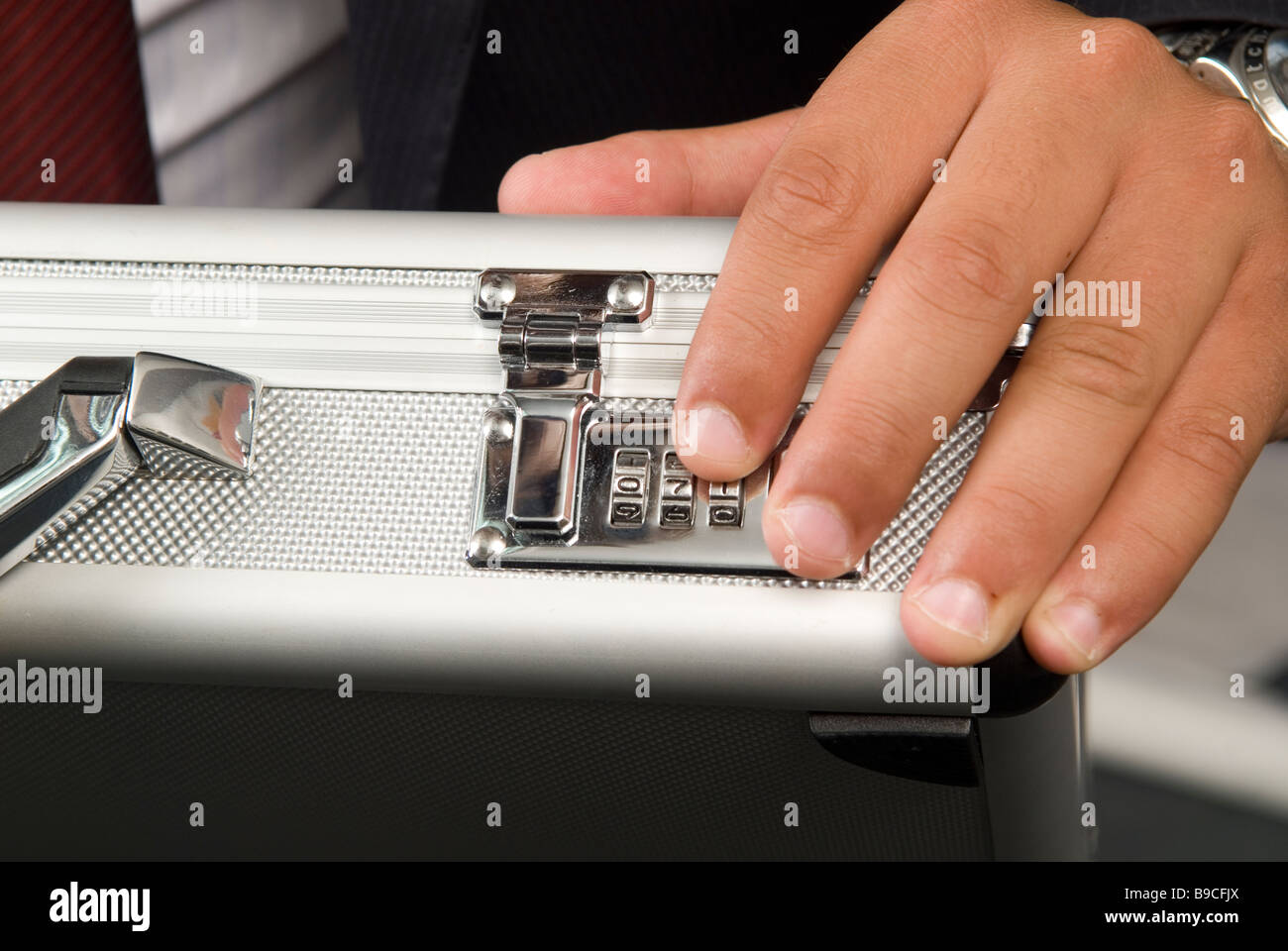 Business man unlocking a combination lock a of a briefcase - Stock Image
