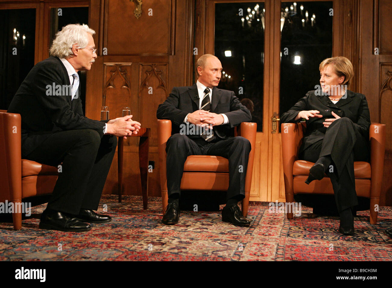 The German based ARD television interviews Vladimir Putin President of Russia center and Angela Merkel Federal Chancellor - Stock Image