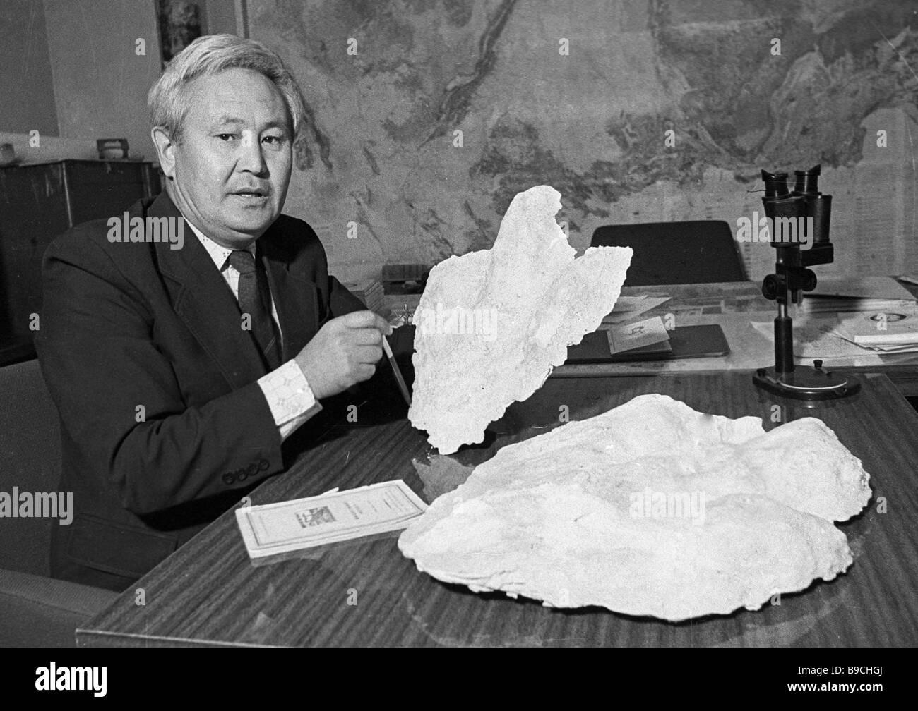 Kurban Amanniyazov Corresponding Member of the Turkmen Academy of Sciences with plaster casts of dinosaur tracksStock Photo