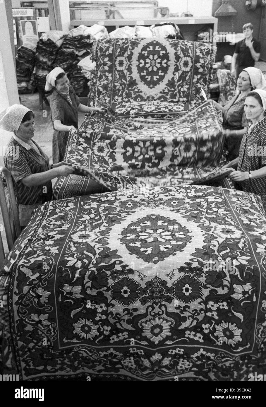 Textile mill workers demonstrate their carpetry - Stock Image
