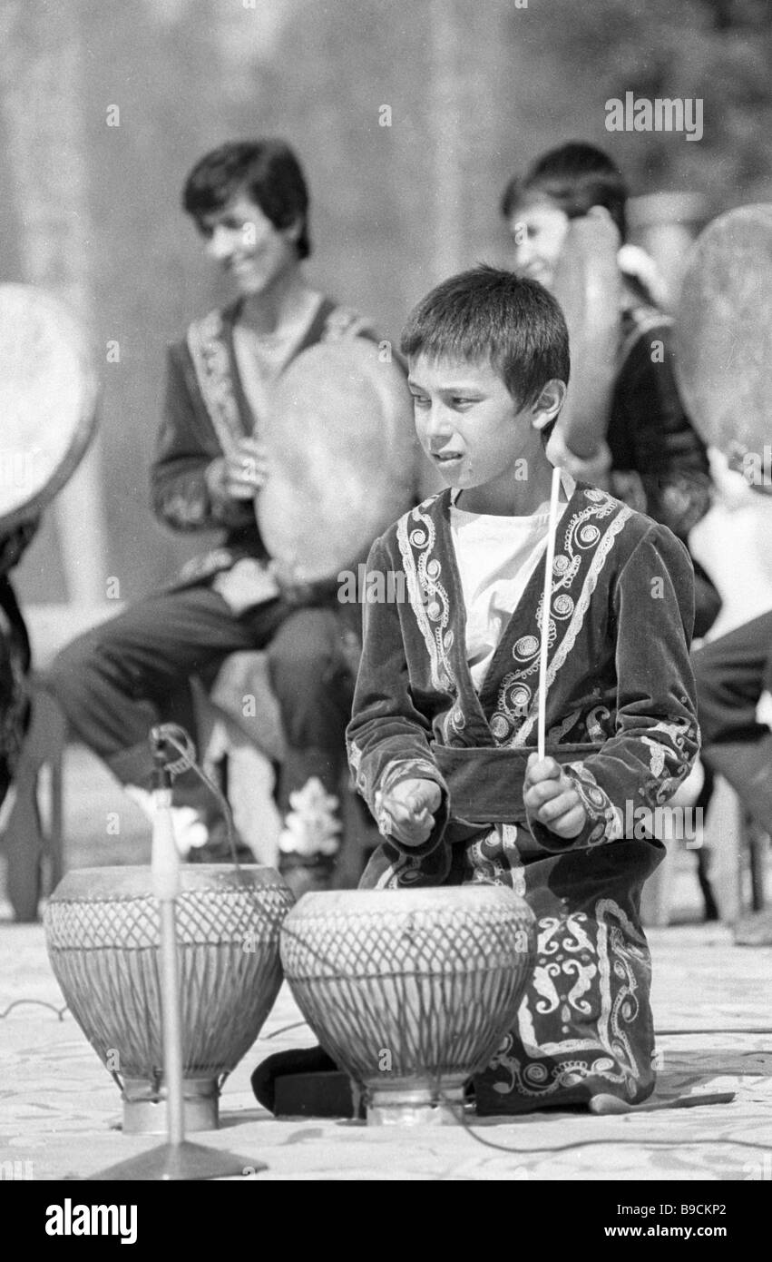Young musician executing folk melodies while playing the ethnic Tajik instrument tavlak - Stock Image