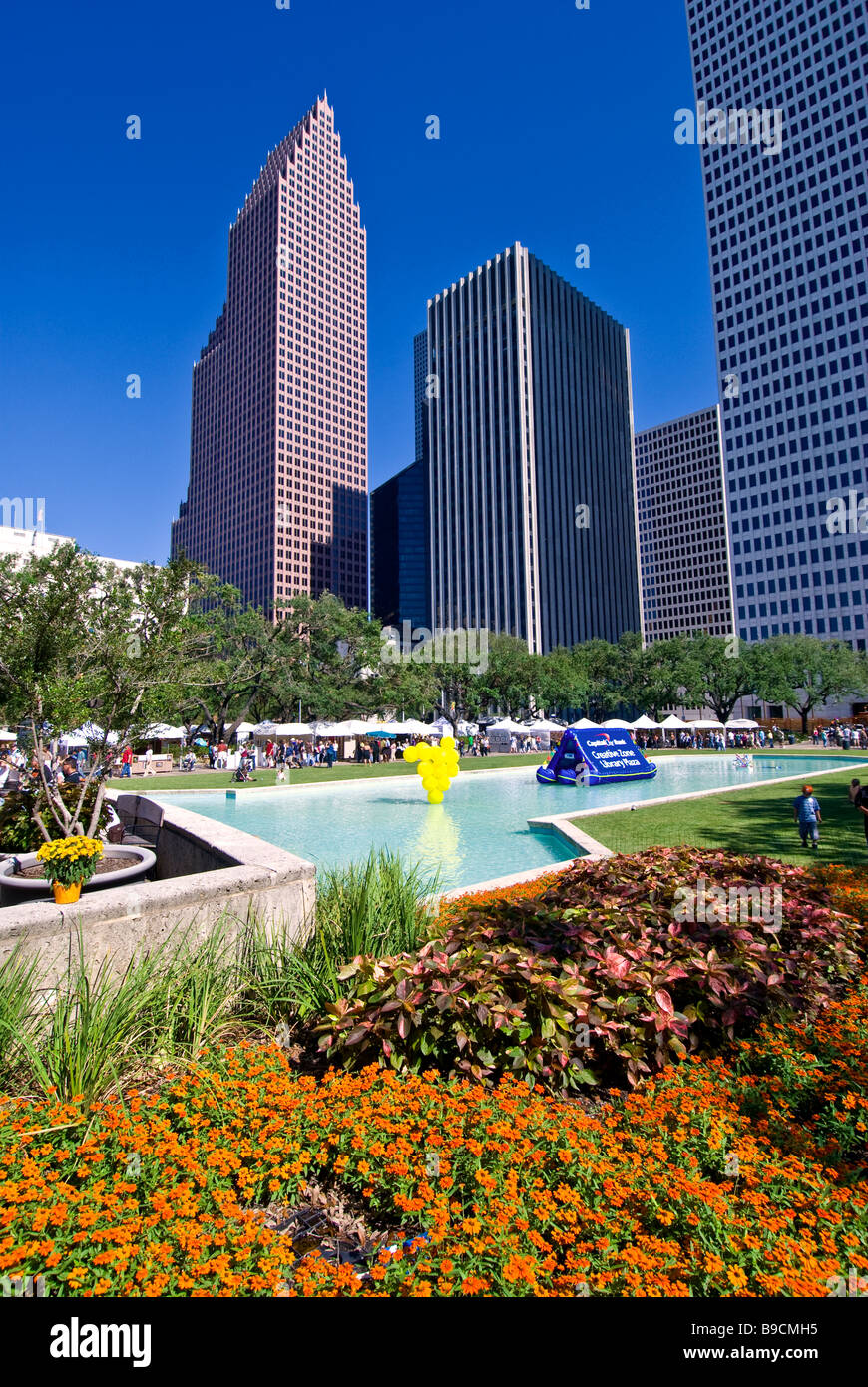Houston Texas downtown skyline red flowers water pond bright colors ideal weather - Stock Image