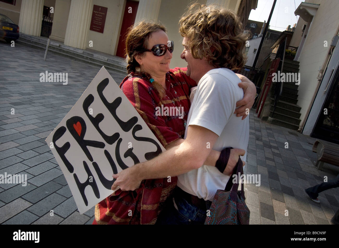 A young couple give each other a spontaneous hug in central Brighton during a 'Free Hugs' event - Stock Image