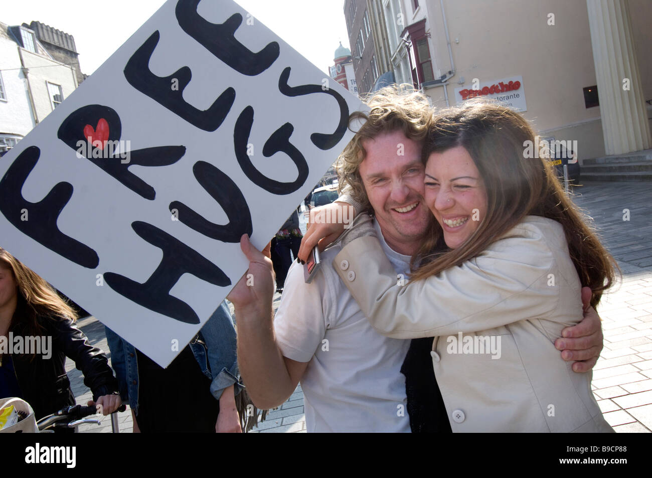 A young couple give each other a spontanious hug in central Brighton - Stock Image