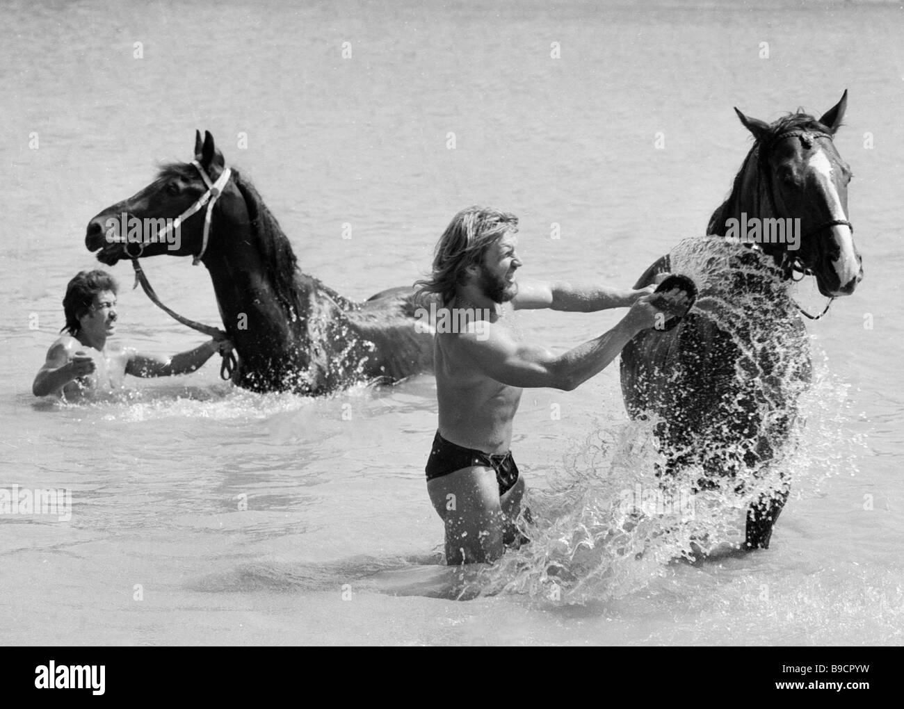 Actors with the Equestrian Theater of Stunt Performers bathing horses - Stock Image