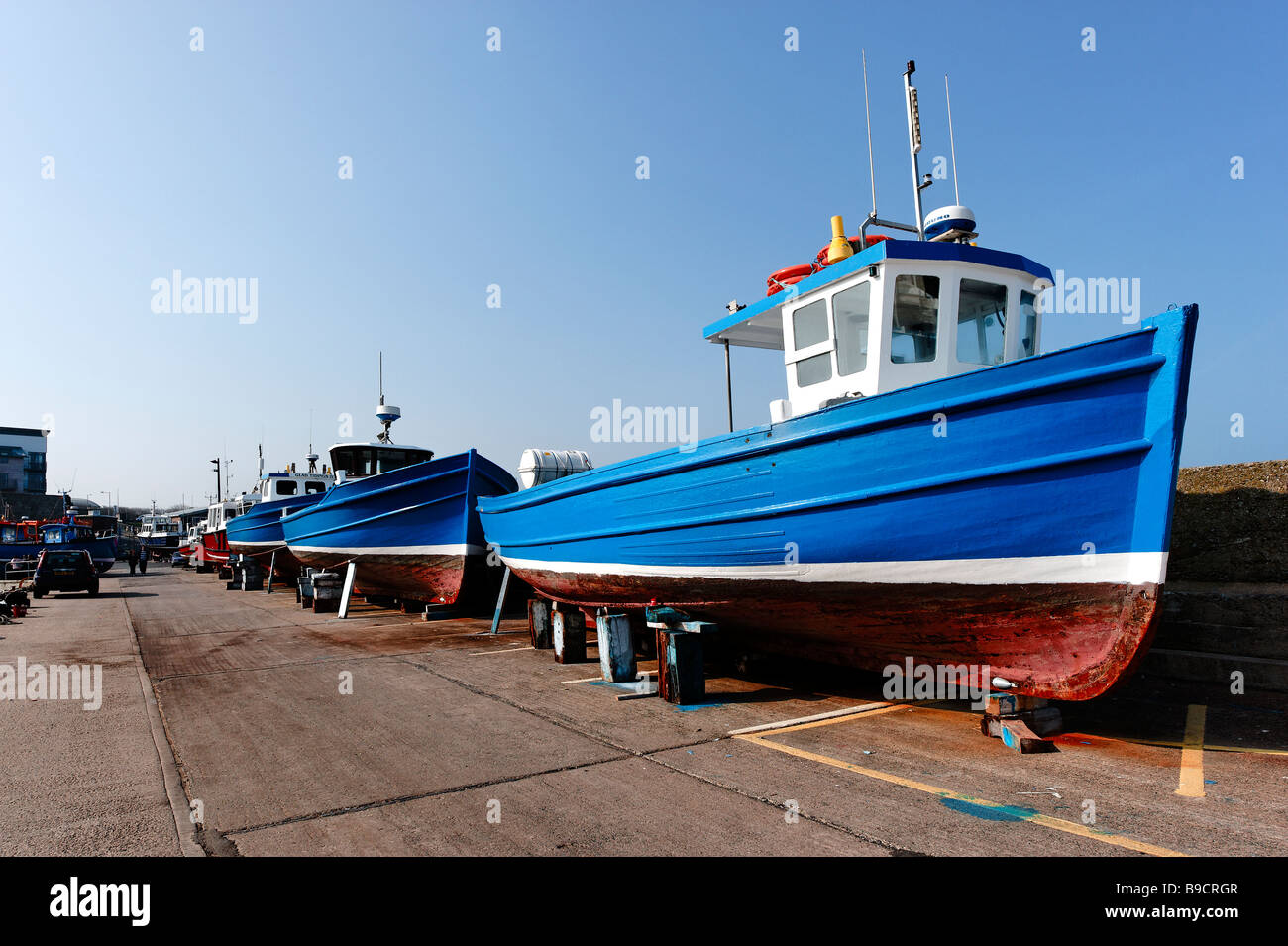 Boats laid up in boatyard in the harbour at Seahouses in Northumberland - Stock Image
