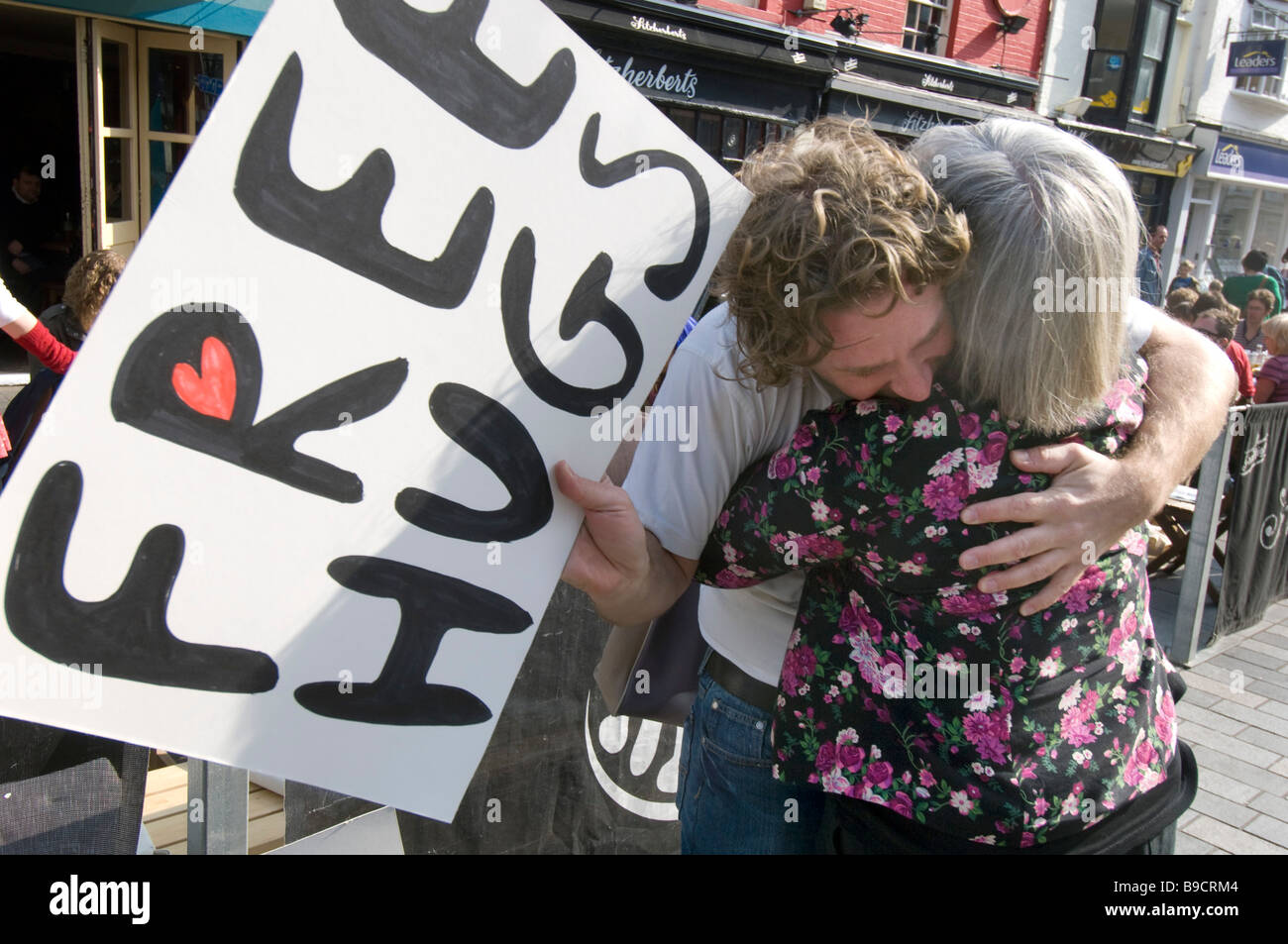 A woman hugs a man holding a sign offering Free Hugs - Stock Image