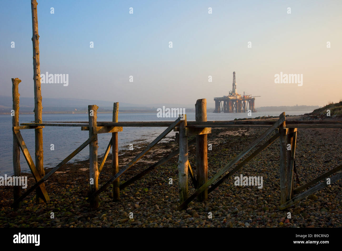 Old Wooden beach jetty & oil rig anchored at Invergordon, Cromarty Firth in northern Scotland, UK - Stock Image