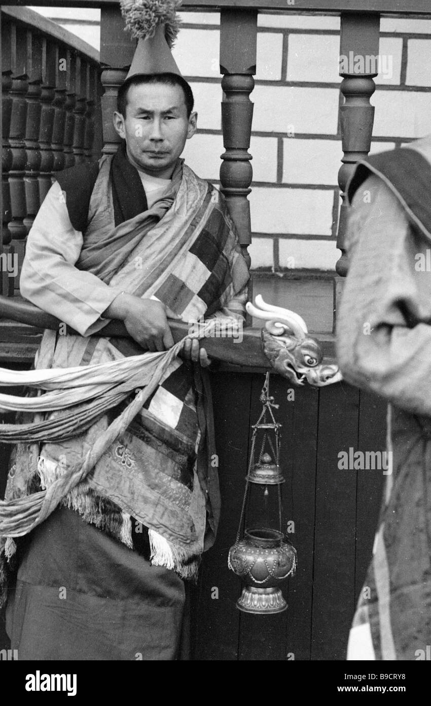 A young lama with an incense burner at the Ivolgino datsan Stock Photo
