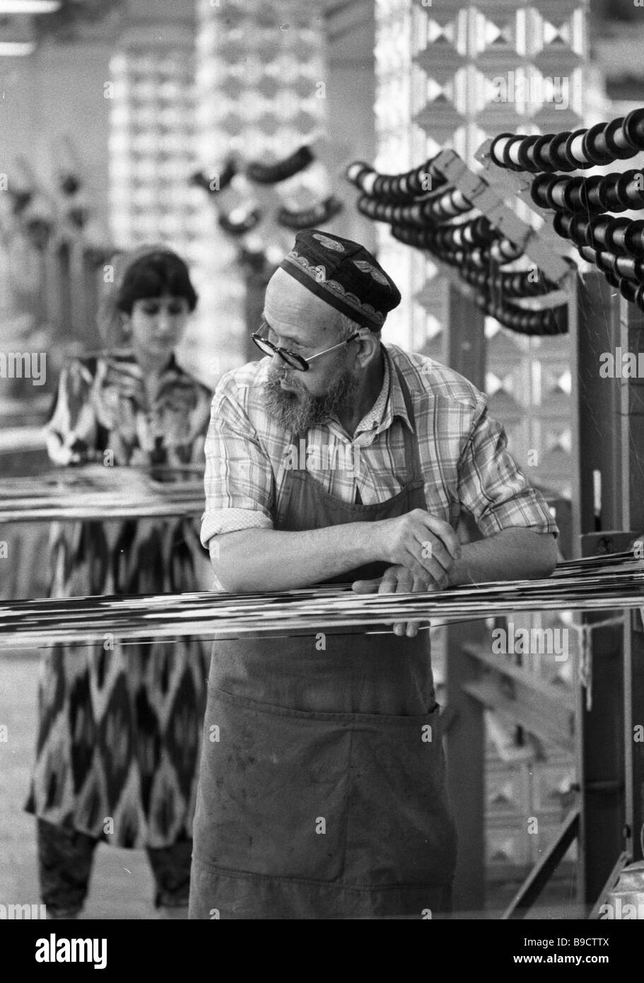 One of the oldest workers of Tajikatlas weaving production enterprise at the loom - Stock Image