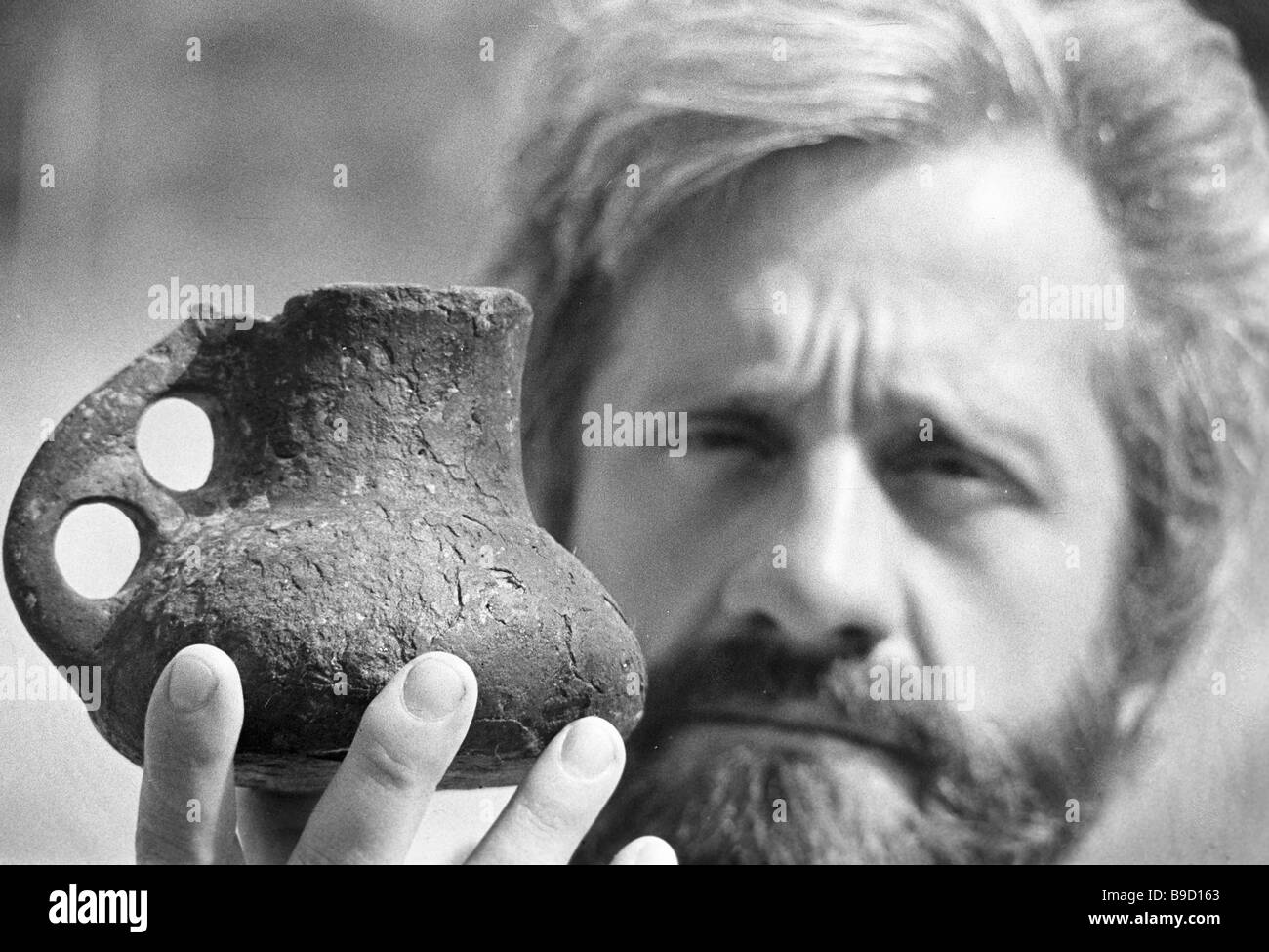 An expedition member of the Institute of Archaeology of the Ukrainian Academy of Sciences demonstrating a ceramic - Stock Image