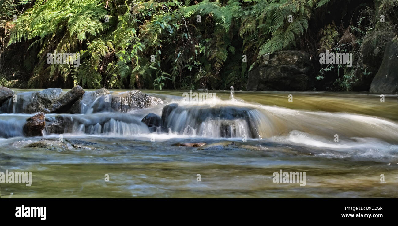 great image of soft water flowing over the rocks in the stream - Stock Image