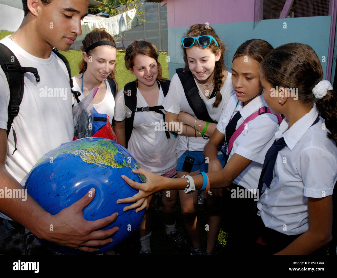 North American teenagers interacting with Costa Rican school children on a cultural exchange trip - Stock Image