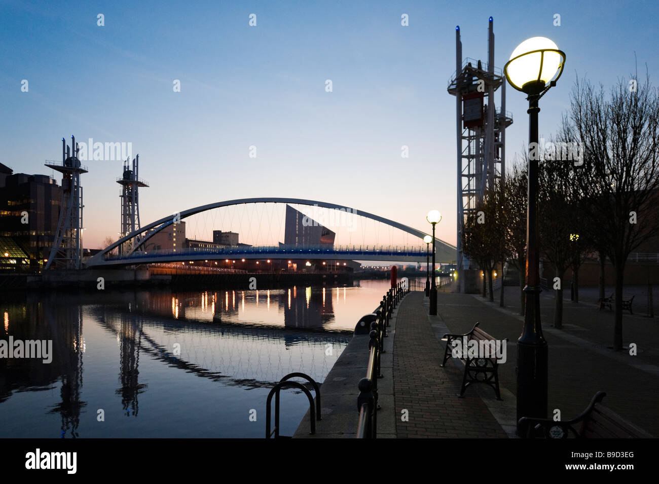 The Millennium footbridge at sunset with the Imperial War Museum North behind, Salford Quays, Greater Manchester, - Stock Image