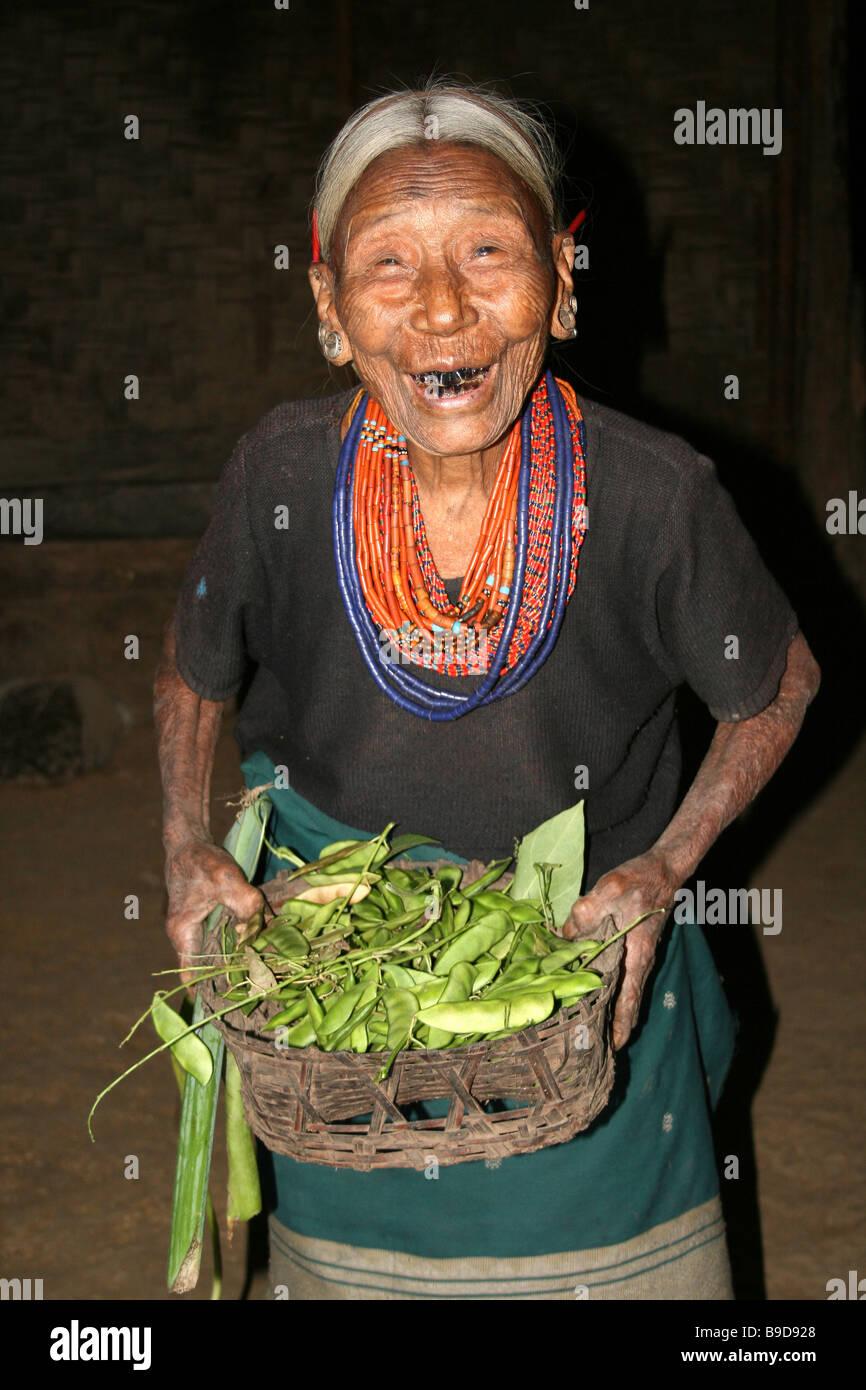 Konyak Naga Tribe Woman laughing and holding basket of Green Beans - Stock Image