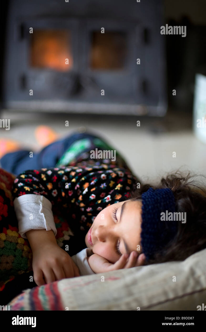 little girl sleeping by the stove - Stock Image
