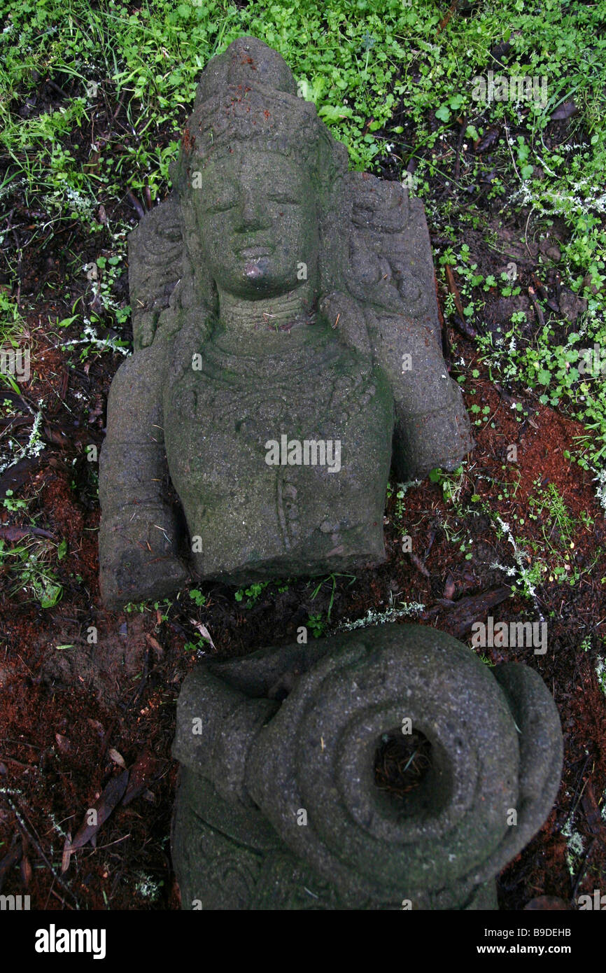 A goddess statue lying on the ground and split in two. - Stock Image
