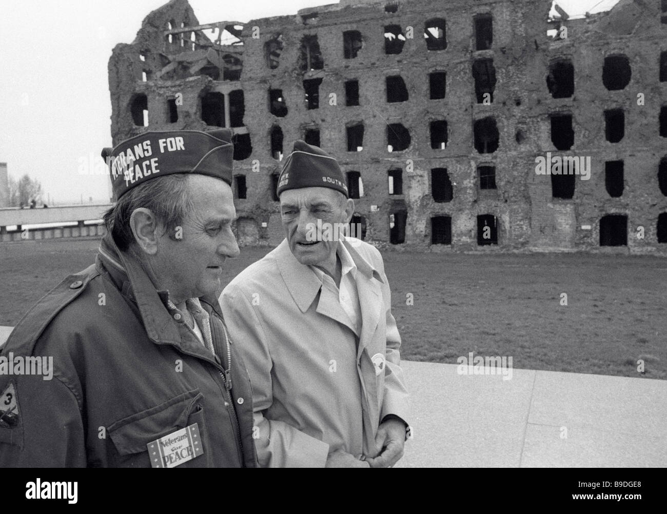 U S veterans of WWII Charles Forster right and Lumir Sabrt left talk near a ruined mill - Stock Image