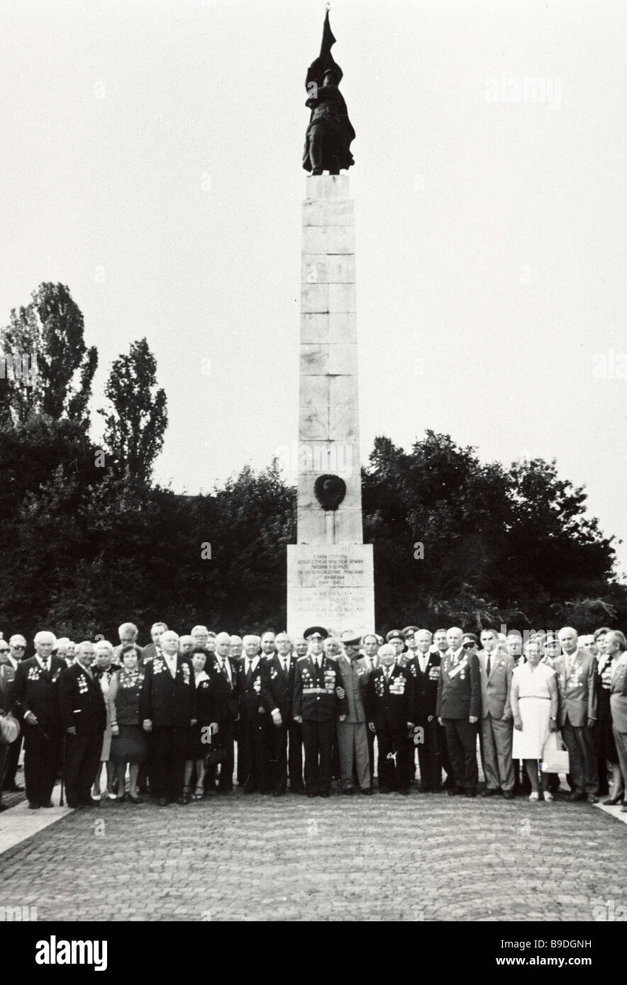 A group of WW II veterans being photographed near the monument to Soviet soldiers who have died for the liberation - Stock Image