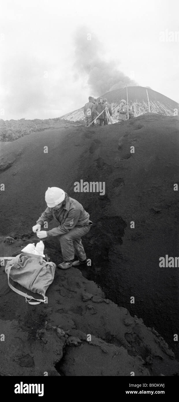 A volcanologist taking ash and lava samples from the Mutnovsky Volcano on Kamchatka - Stock Image