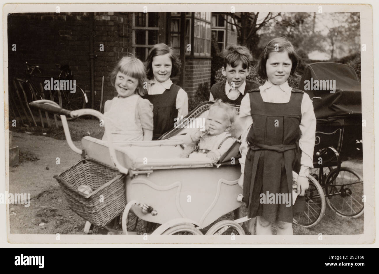 Cheeky young children with prams looking after a baby outside their home in the 1950's Stock Photo