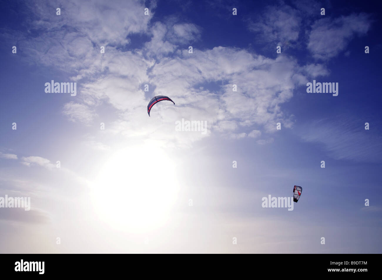 Pair of Power Kites Against Sun and Blue Sky - Stock Image
