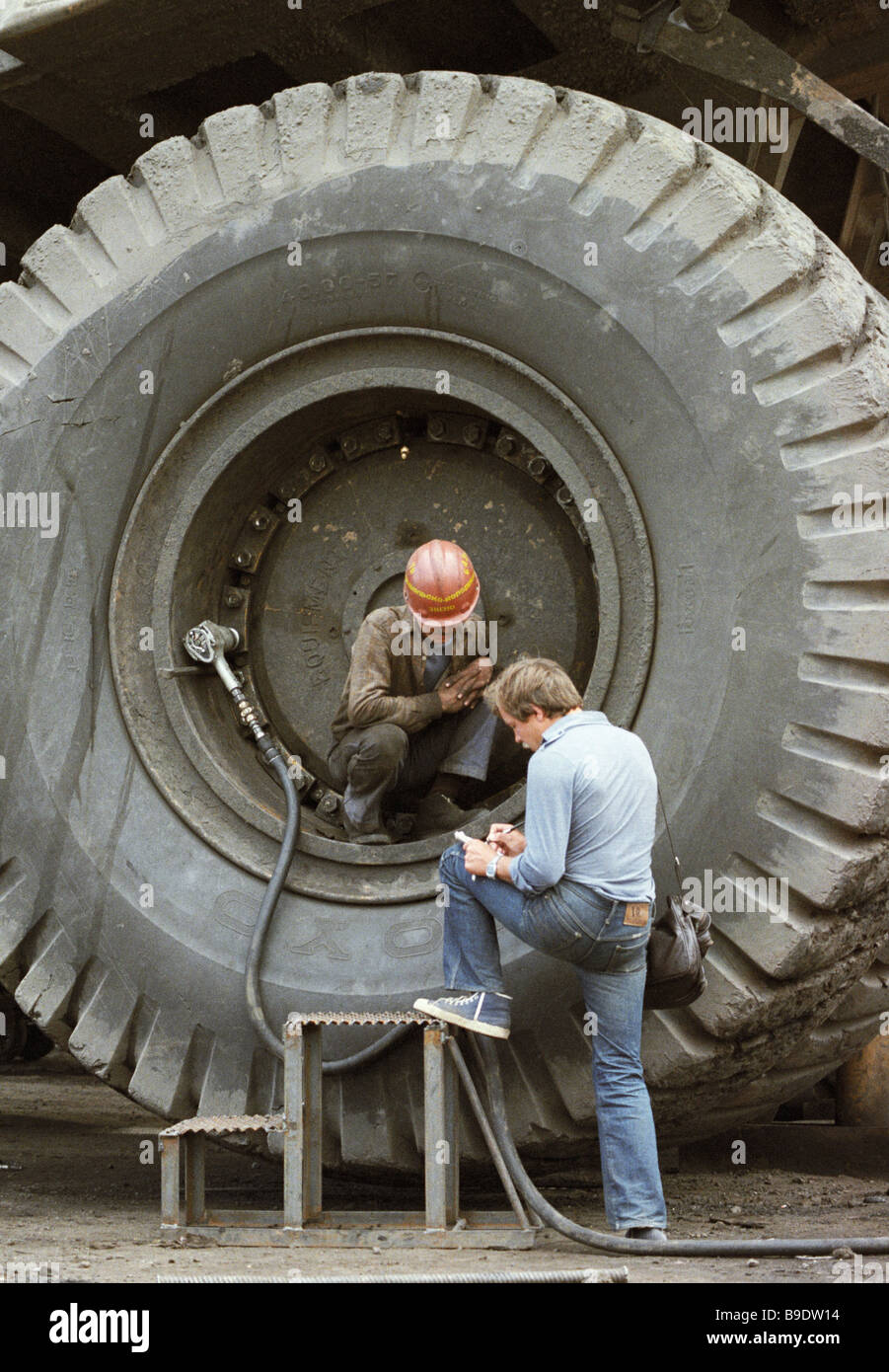 Correspondent interviews worker in front of huge wheel - Stock Image