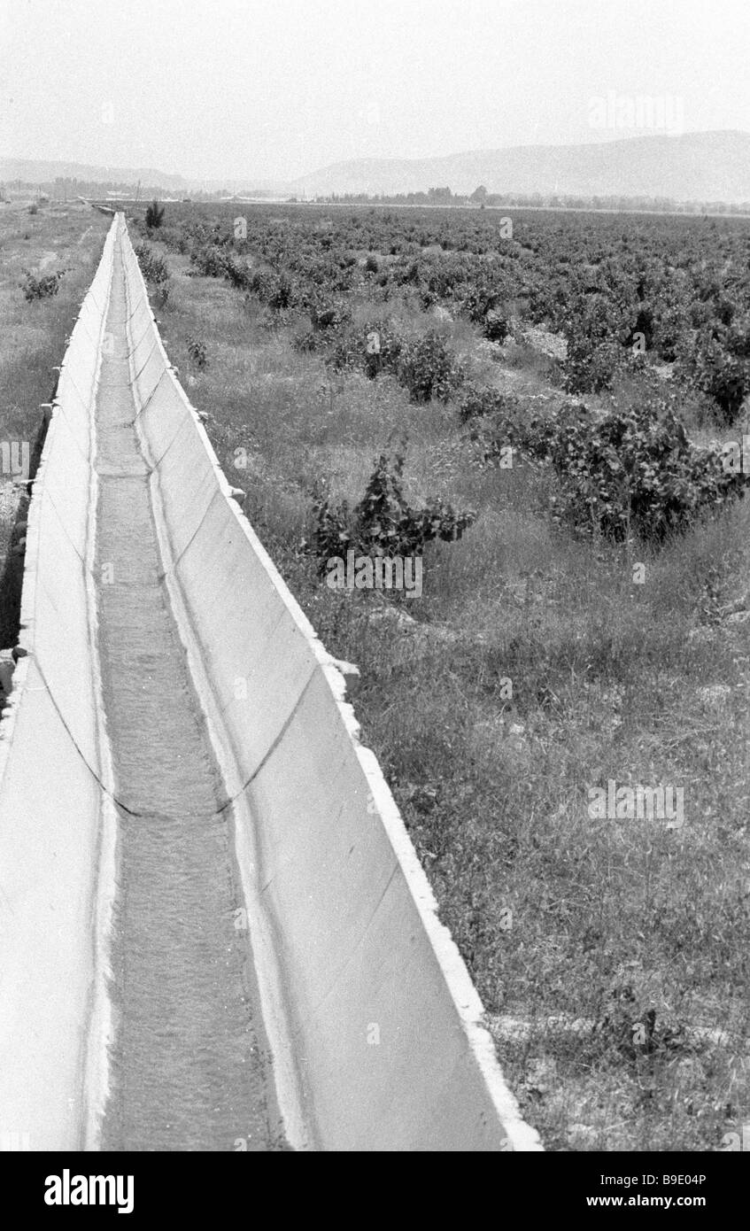 Concrete troughs of which irrigation ditches are made in Zafarabad district They cut losses of cherished water by Stock Photo