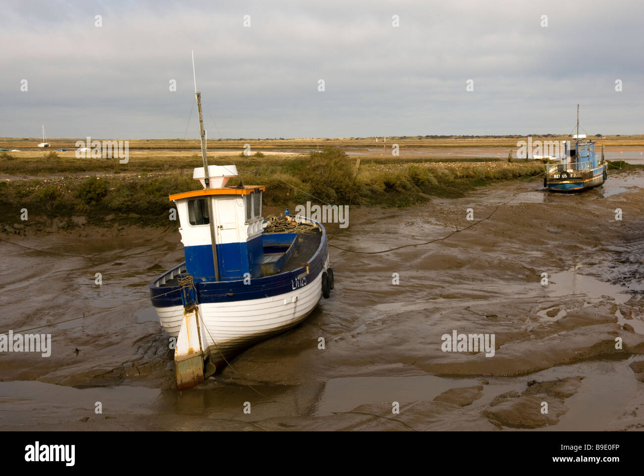 Fishing boats moored on the saltings salt marshes at Brancaster Staithe Norfolk England Stock Photo