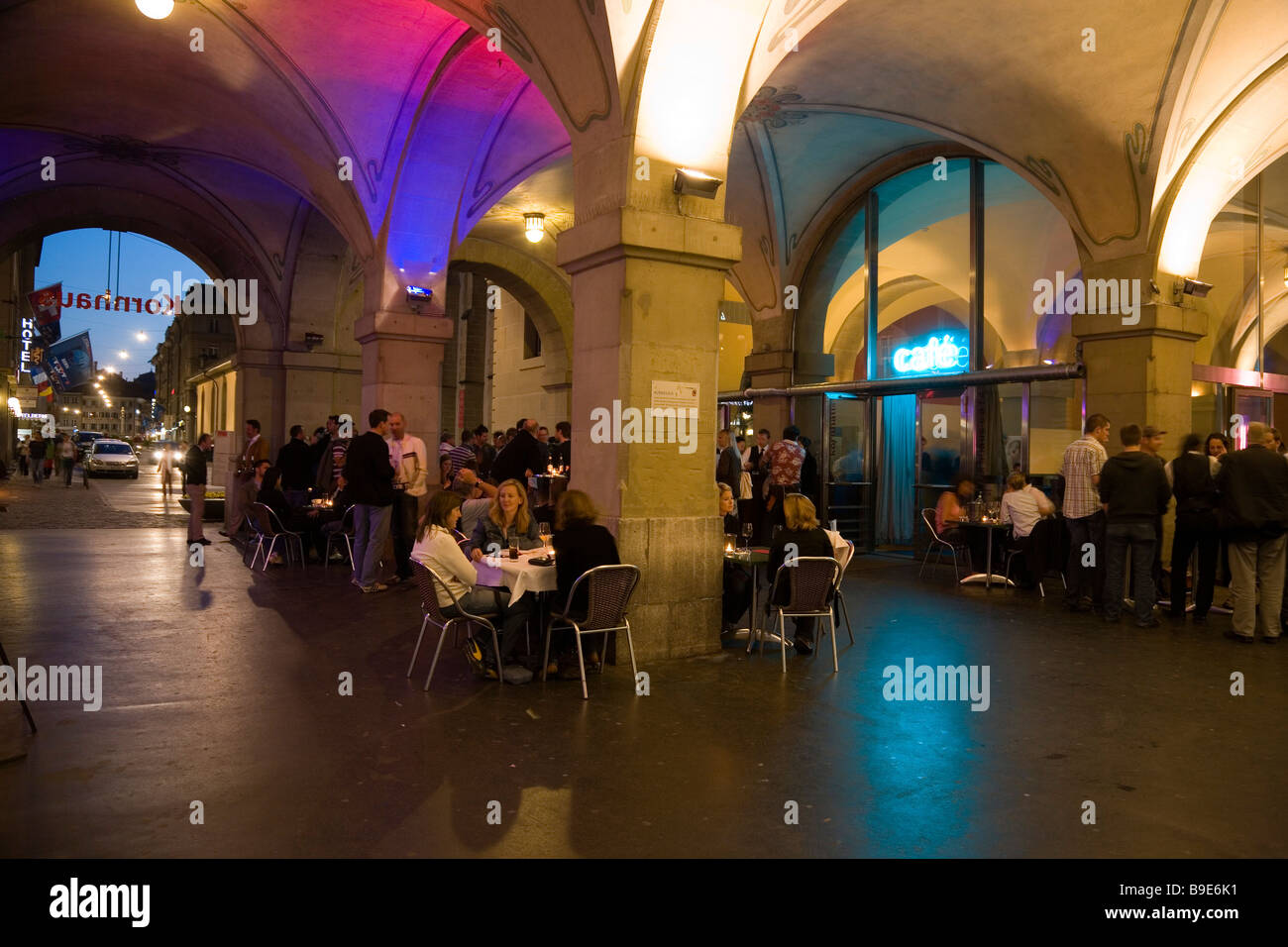 Guests sitting under arcades outside the restaurant Kornhaus in the evening Old Town Berne Canton of Berne Switzerland - Stock Image