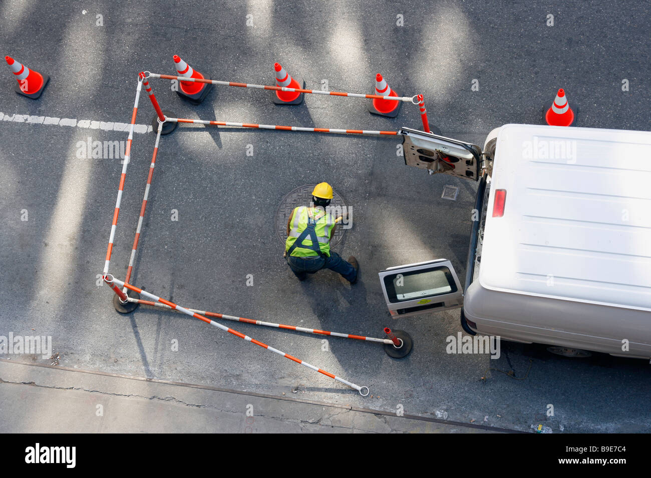 Maintenance worker closing a manhole cover with a mallet. - Stock Image
