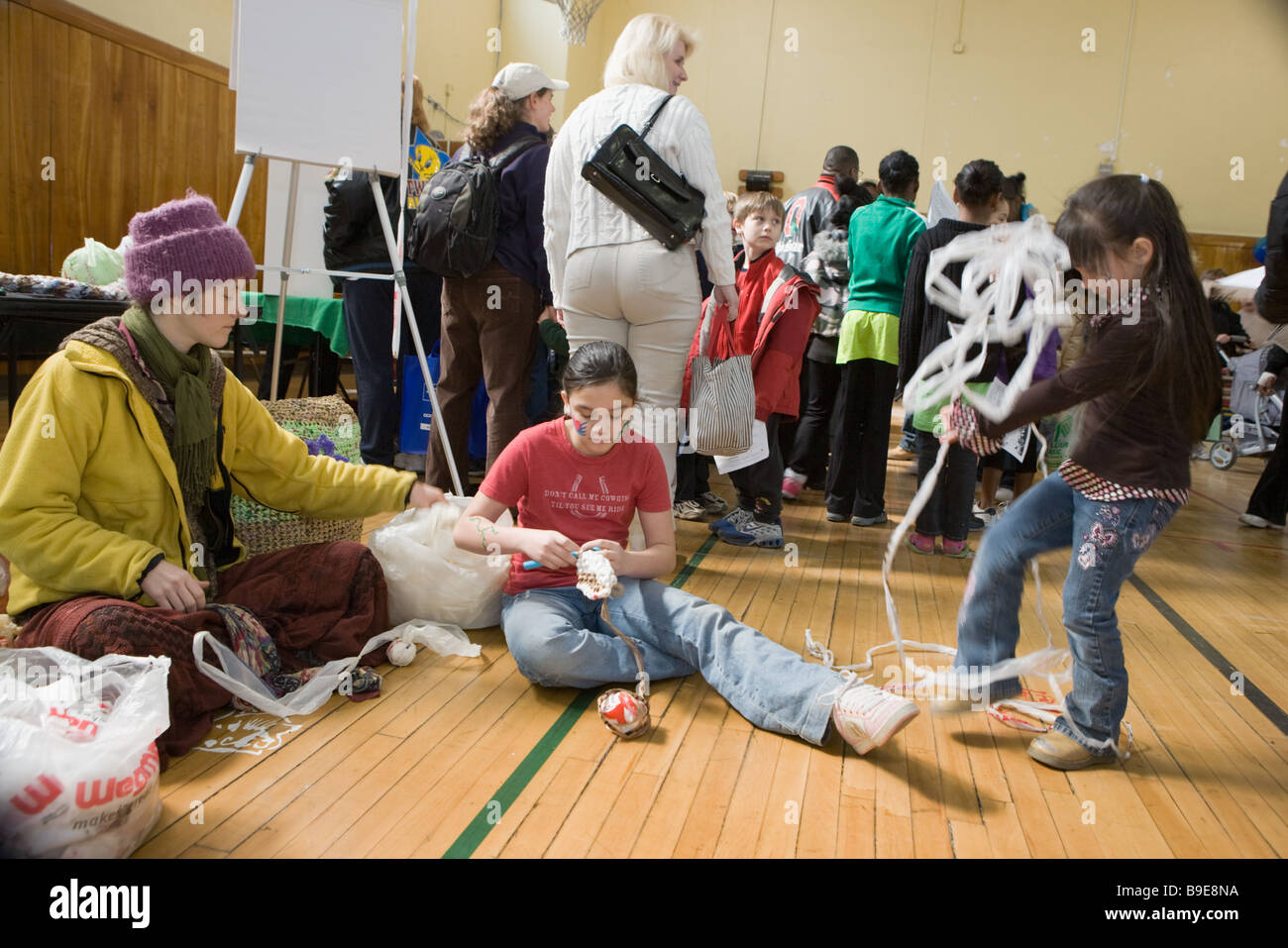 Woman teaching kids how to crochet using recyclable plastic at a Green Fair in Syracuse New York - Stock Image