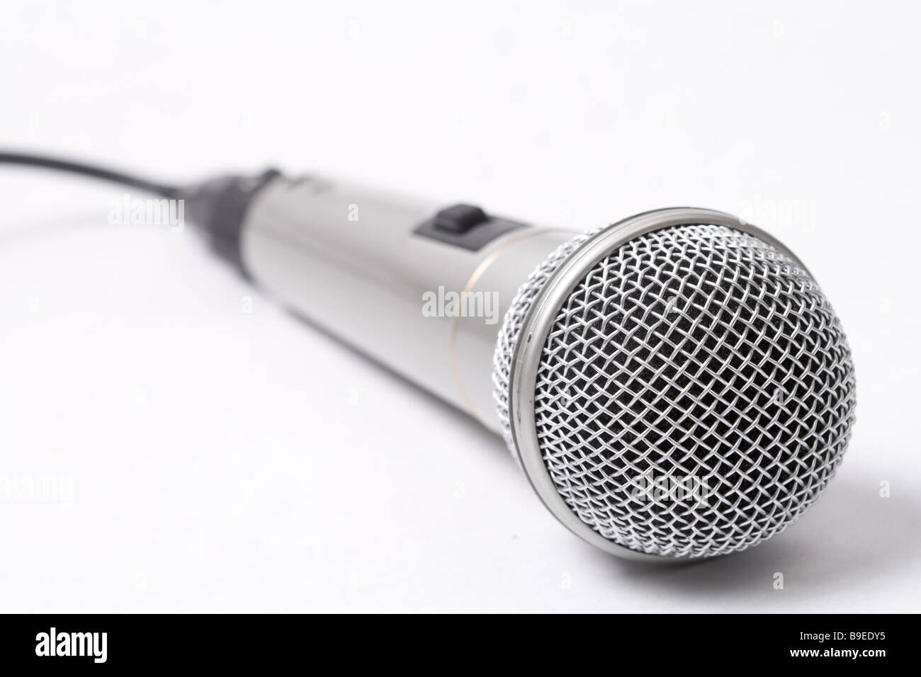 Closeup on metallic microphone over white background - Stock Image