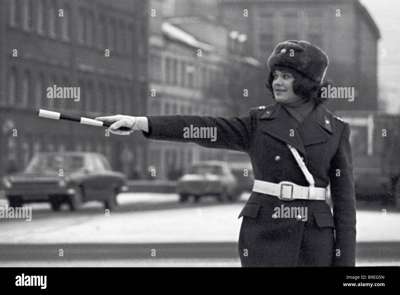 A traffic controller directing traffic with a baton - Stock Image